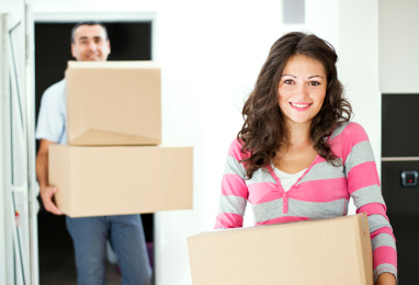 couple moving into apartment carrying boxes